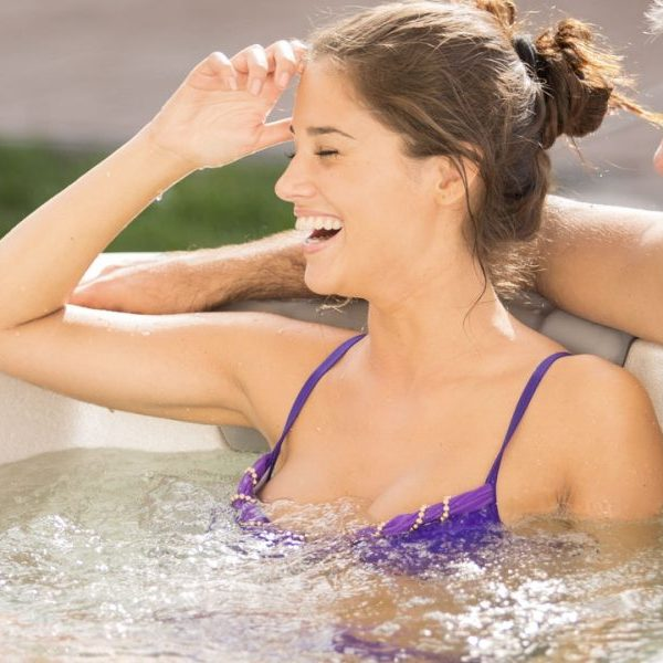 Wellis Kilimanjaro premium spa whirlpools with two young smiling couple. Cameo jacuzzi shell color.